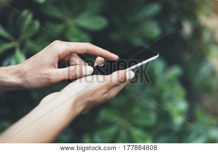 Female hands using smartphone isolated on background green nature wall mockup hipster manager holding mobile gadget person text message outside connect content close mock up