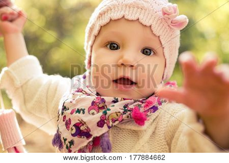 Closeup portrait of beautiful baby girl wearing stylish hat and cozy sweater. Outdoors spring, autumn photo. Seasonal clothes. Childhood.