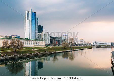 Minsk, Belarus - April 6, 2016: Sunset over central district Nemiga in Minsk, Belarus. Reflection of Pobediteley Avenue in rivers water
