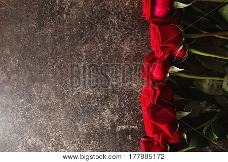 Rose flower lie on a dark marble table. Big beautiful bouquet of red rose flower. Texture colors. A gift for a wedding birthday Valentine's Day. Space for text and design. Flat lay flower copyspace.