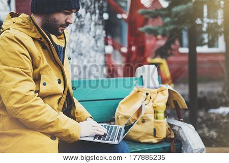 Hipster with yellow backpack jacket cap thermo cup of coffee using computer open laptop in spring street outdoor tourist man typing on keyboard traveler connect wifi internet freelance process in workspace
