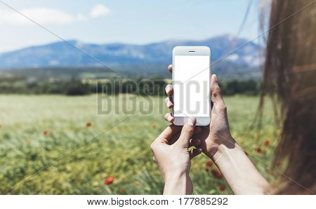 Hipster photograph on digital smart phone or technology mock up of blank screen. Girl using mobile on red poppies flowers and cones background close. Hands holding gadget on blurred backdrop front view