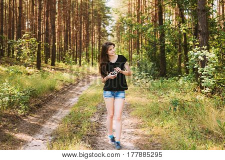 Happy Red-haired Caucasian Girl Young Woman Photographer Walking And Taking Pictures The Old Retro Vintage Film Camera In Summer Green Forest. Girl Dressed In A Black T-shirt.