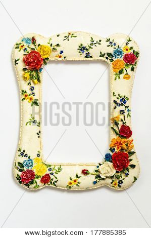 An old white frame with a pattern of red flowers. Isolated over white background