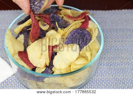 Adult male fingers picking up one of each of three colors of potato chips. Yellow red and purple potato chips chosen by fingers of an adult male.