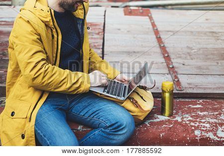 Hipster with yellow backpack jacket cap drink coffee of thermo cup freelance using computer open laptop in spring street outdoor tourist man typing on keyboard traveler connect wifi internet process in workspace