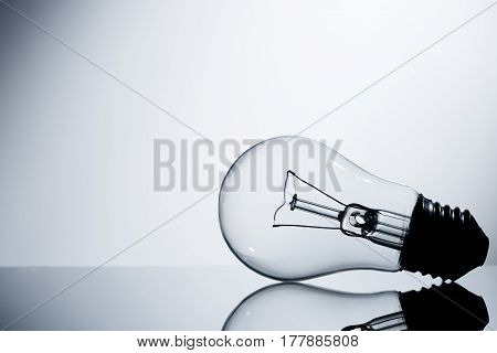 Incandescent Lamp Lying On A Table On A Gray Gradient Background