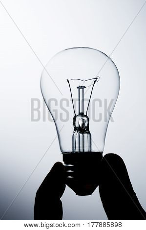 Incandescent Lamp In A Hand On A Gradient Background