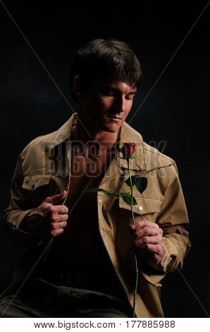 The very handsome man is smelling a rose.