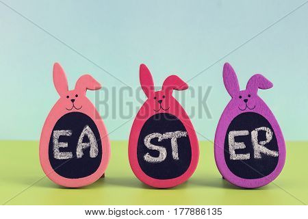 Written word Easter on three Bunny Eggs on blue and green colored background. Greeting card concept negative space