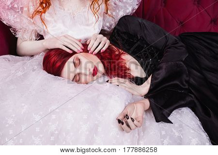 Two fairy girls with red hair in retro dress in the bedroom. Femme fatale in a black dress and nice girl in white wedding dress. Fairy and Witch. Model posing in studio. Historical renaissance fairy dresses.
