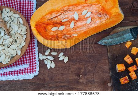 piece of pumpkin and pumpkin seeds on a brown wooden table an empty space in the middle