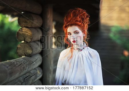 Beautiful red-haired girl with a high hair in an old white dress in the park. The Victorian era. Historic victorian costume. White victorian Queen. Princess castle
