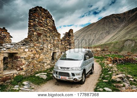 Ketrisi village, Georgia - May 22, 2016: Mitsubishi Delica Space Gear On Country Road Near Old Abandoned Ruined Houses In Truso Gorge, Kazbegi District, Mtskheta-mtianeti Region, Georgia