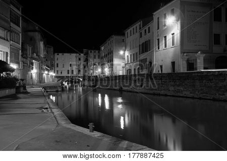 Urban streets, night scene and architecture with poem od Pierre Reverdy on building end wall monochrome buildings along sides of Canal de le Robine and Merchants Bridge at end, Narbonne, France.