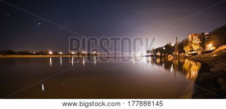 Night sky. The ship is in the water. The beautiful night scenery. Slow shutter speed. Spectacular clear starry sky. Scenic view. The bridge over the river. The port on the river bank. Night city