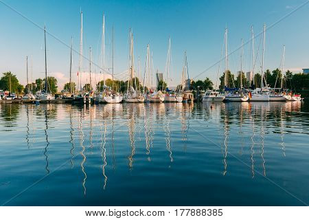 Riga, Latvia. Many Yachts Moored At The City Pier Harbour Bay And Quay In Summer Sunny Evening. Reflections From Boats In The Water Of Western Dvina River.