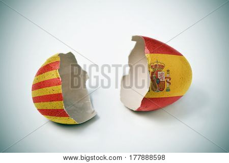 the two halves of a cracked eggshell, one patterned with the flag of Catalonia and the other one patterned with the flag of Spain