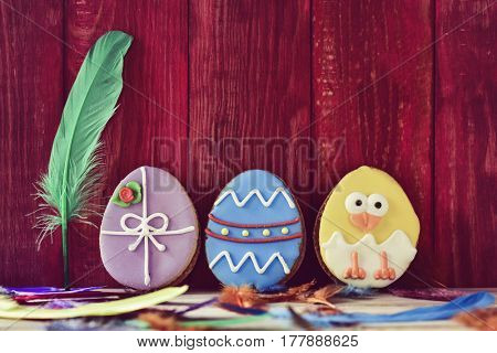 a pile of different some cookies patterned as different decorated easter eggs against a red wooden background, and feathers of different colors sprinkled on a rustic surface