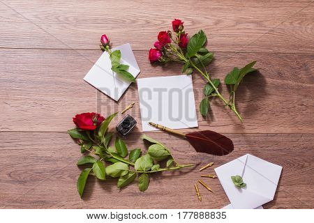 Fountain pen and ink on wooden background. White envelope and red roses. Greeting card. Conceptual photography with pen. Wedding invitation card. Valentine day. Tips to pen. Flat lay copyspace mock up