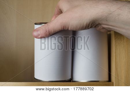 Male hand reaching up to shelf to select one of two unbranded items stored in tin cans. Plain white labels provide copy space.
