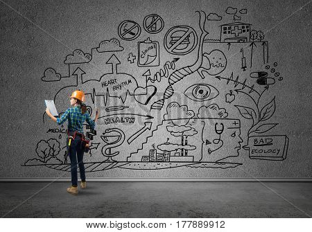 Back view of engineer woman in hardhat and sketched concept on wall