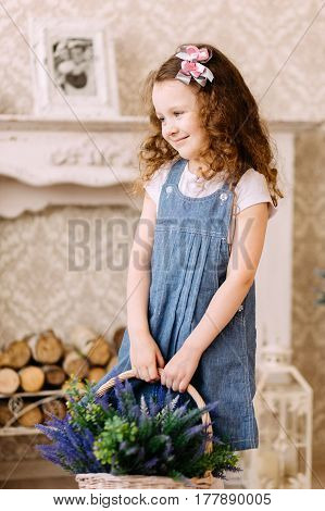 Girl with curly hair smiling and posing with wicker basket with flowers. Mother day concept