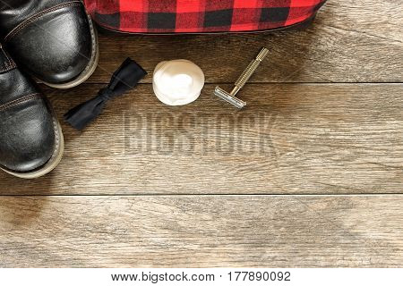 Masculine beauty and fashion items frame open wood background with room for copy.