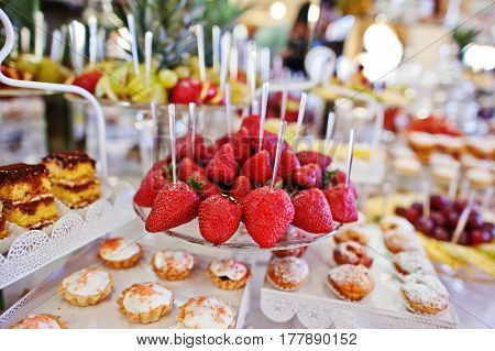Strawberries At Wedding Reception Table With Different Fruits, Cakes And Sweets.
