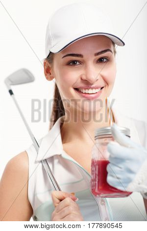 Pretty girl golfer posing with with jar of detox juice on white backgroud in studio