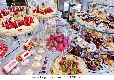 Strawberries Under Glass Case At Wedding Reception Table With Different Fruits, Cakes And Sweets.