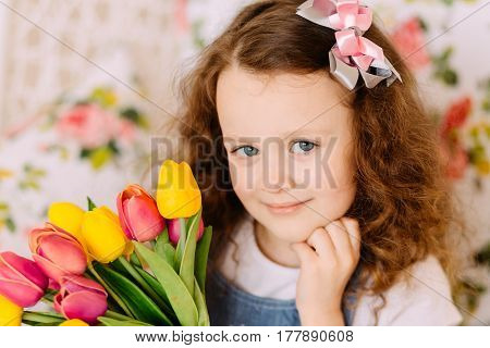 Girl with curly hair smiling and posing with a large bouquet of flowers. Mother day concept