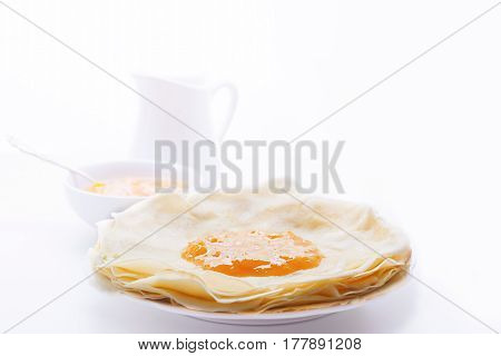 Crispy crepes with apricot jam on a white plate