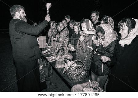 Dobrush, Belarus - May 1, 2016: The priest and the parish happy. Easter night service