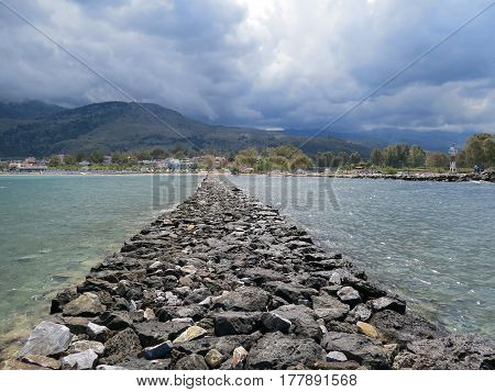 Laid in the sea road from stones on a background of mountains and low clouds near the village of Georgioupoli, Crete, Greece