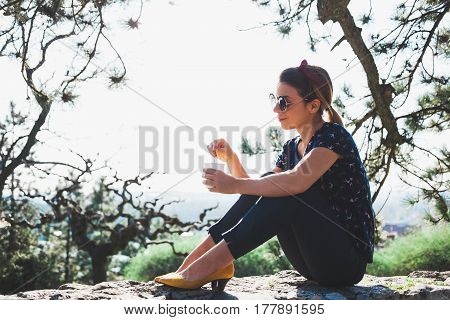 Young woman enjoying coffee in the park