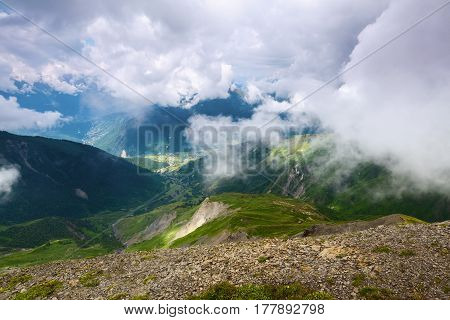 Alpine scenery with big mountains covered with glaciers fog and green lawns with different flowers trails and sky on a summer day. Upper Svaneti Georgia Europe.