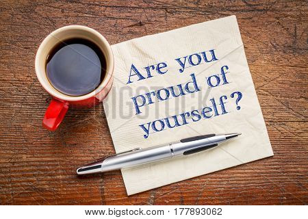 Are you proud of yourself question - handwriting on a napkin with a cup of espresso coffee