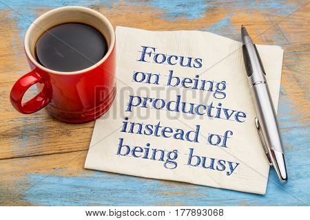Focus on being productive instead of being busy - handwriting on a napkin with a cup of espresso coffee