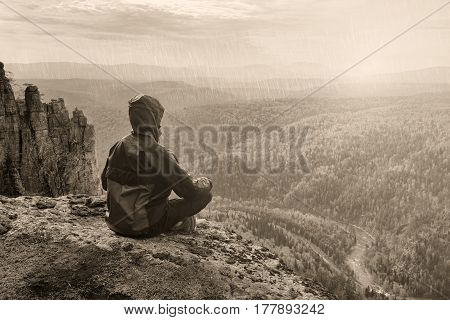 Man hiker sitting on top of mountain in meditation pose and thinking, black and white toned picture