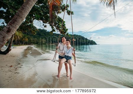 Mother and daughter sit on Swing tropical beach phu quoc