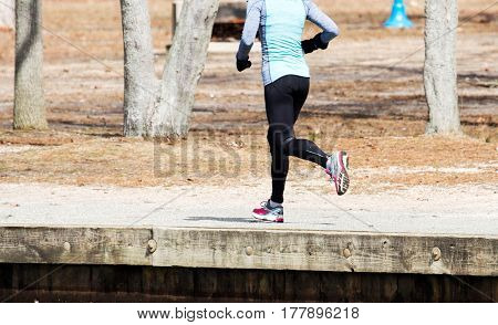A female runner is running around a lake on a cold day in March