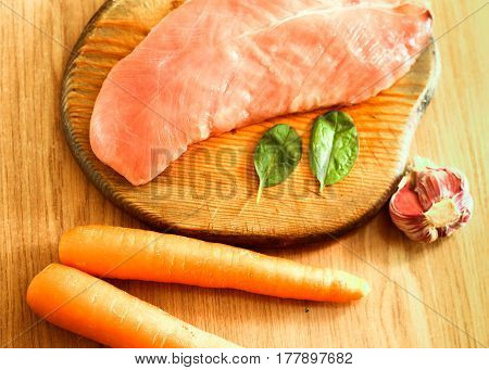 Raw Chicken Fillet Meat With Fresh Vegetables (garlic, Two Carrots, Green Basil Leaves) On Wooden Bo
