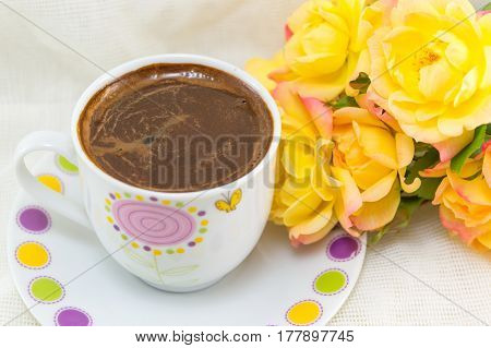 Cup Of Coffee On A Table Decorated With Roses