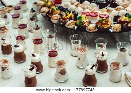 Cute candybar with various candies and cakes. Wedding sweets on glas stand