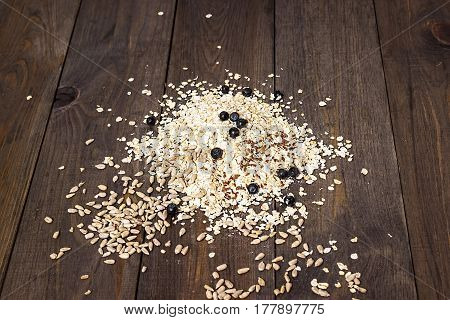 Muesli. Rolled oats, sunflower and flax seeds and blueberries on a dark brown wooden background.