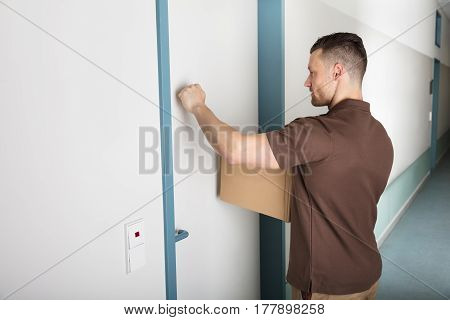 Close-up Of A Delivery Man Holding Cardboard Box Knocking The Door