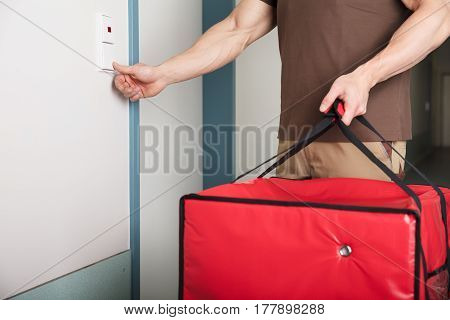 Pizza Delivery Man Ringing The Door Bell With A Large Red Bag In His Hand
