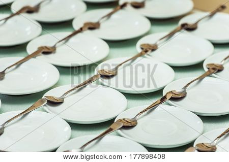 Rows of clean white dish and spoon in a restaurant ready to serve