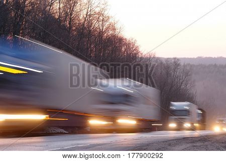 Trucks on a highway in an evening